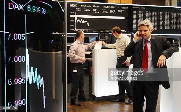Stock traders go about their business on the floor of the Frankfurt stock exchange 21 February 2007 as the daily graph of the German share index DAX...