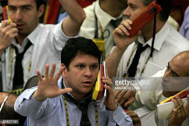 Stock traders negotiate in the future dollar pit prior to the morning closing time at the Mercantile Futures Exchange in Sao Paulo Brazil on...