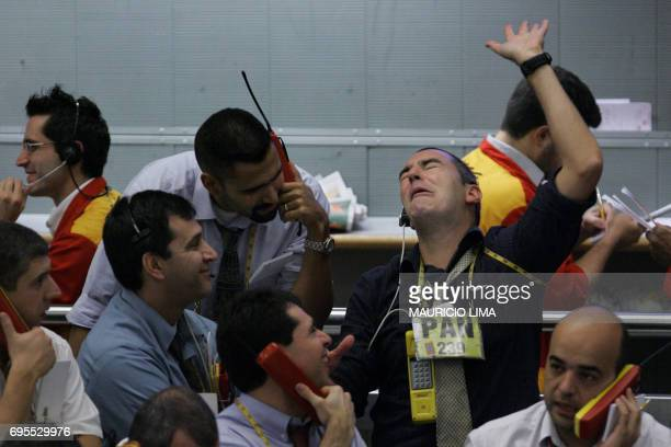 Stock traders share a joke as they negotiate in the future dollar pit during the morning session at the Mercantile Futures Exchange in Sao Paulo...