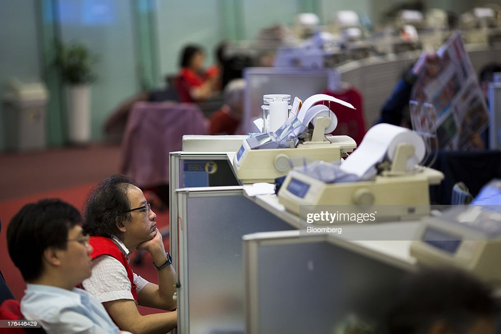 Stock traders sit at their desks on the trading floor of the Hong Kong Stock Exchange in Hong Kong, China, on Tuesday, Aug. 13, 2013. Hong Kong Exchanges & Clearing Ltd., operator of the Hong Kong Stock Exchange, is scheduled to release second-quarter results tomorrow. Photographer: Jerome Favre/Bloomberg via Getty Images