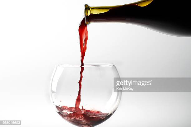 Stock wine photo of a glass of red wine being poured from the bottle