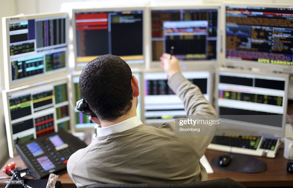 A stockbroker gestures while monitoring financial data on his computer screens at Shore Capital Group Ltd. brokerage in London, U.K., on Thursday, March 28, 2013. Cyprus's banks opened for the first time in almost two weeks, with new rules curbing access to cash preventing an initial panic to withdraw deposits. Photographer: Chris Ratcliffe/Bloomberg via Getty Images