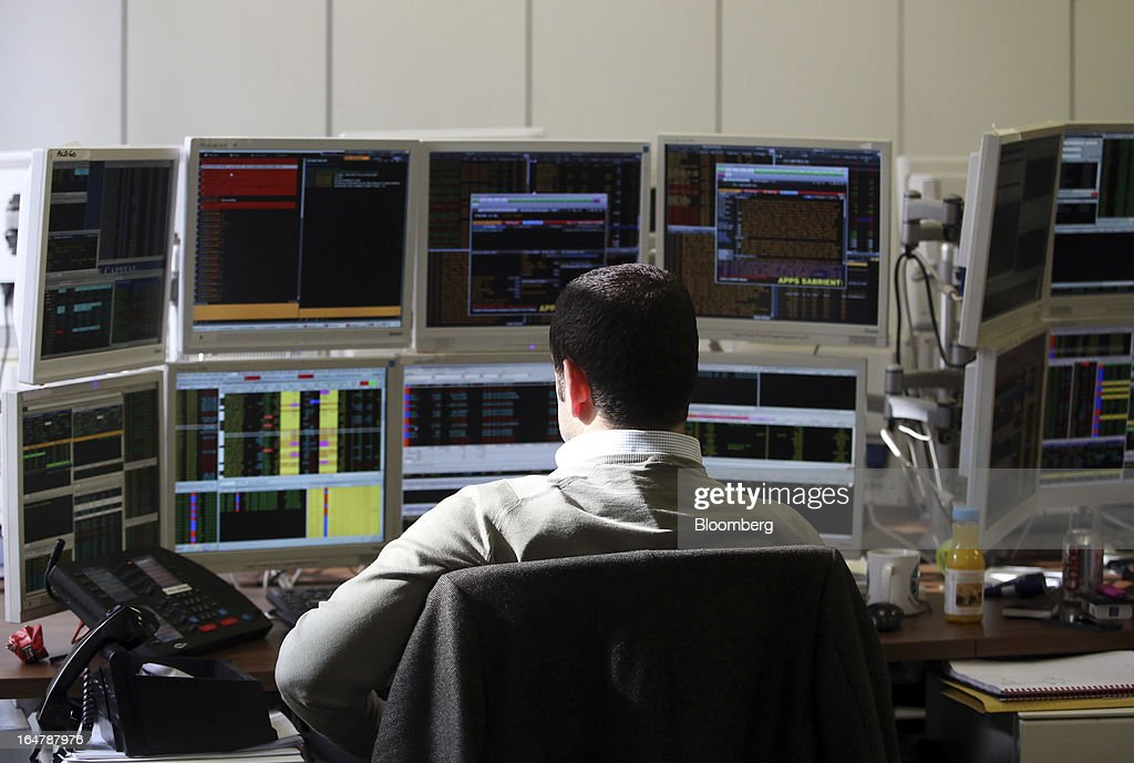 A stockbroker monitors financial data on his computer screens at Shore Capital Group Ltd. brokerage in London, U.K., on Thursday, March 28, 2013. Cyprus's banks opened for the first time in almost two weeks, with new rules curbing access to cash preventing an initial panic to withdraw deposits. Photographer: Chris Ratcliffe/Bloomberg via Getty Images