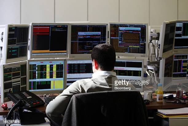 A stockbroker monitors financial data on his computer screens at Shore Capital Group Ltd brokerage in London UK on Thursday March 28 2013 Cyprus's...