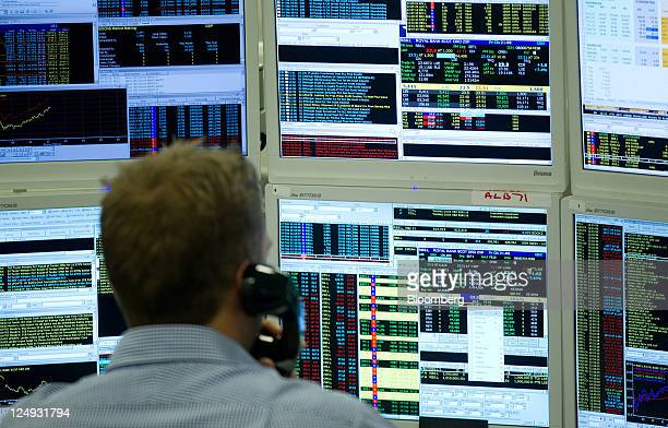 A stockbroker monitors stock prices on his computer screens at Shore Capital Group Ltd in London UK on Wednesday Sept 14 2011 Stocks rose sending the...