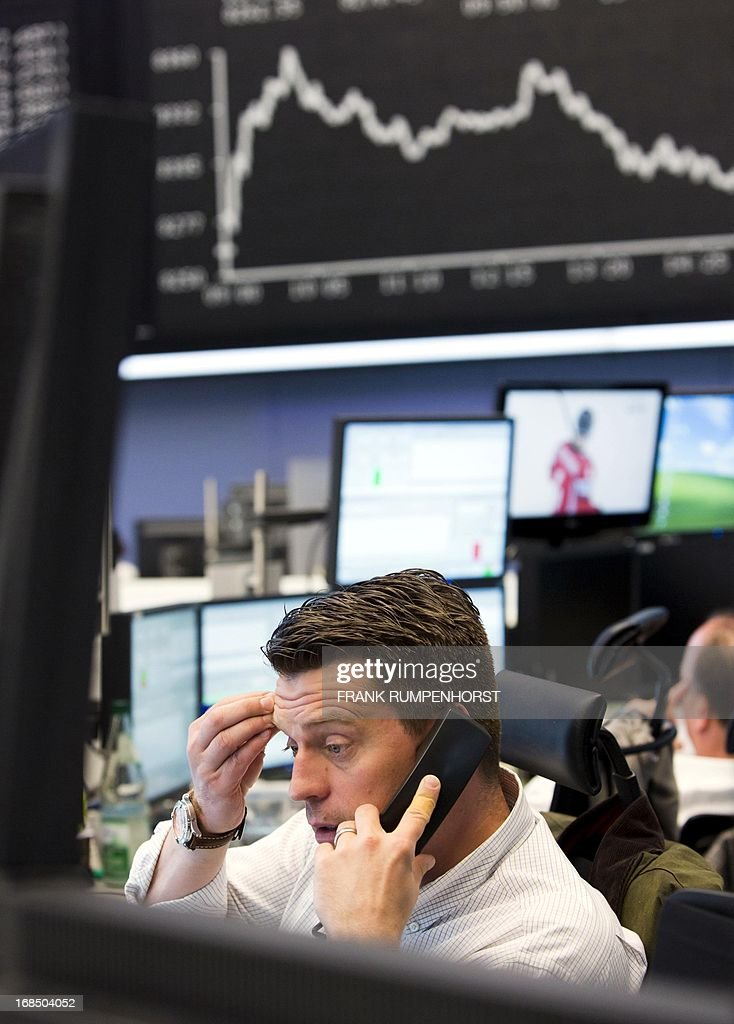 A stockbroker speaks on the phone in front of display showing the German Stock Market Index DAX is seen at the stock exchange in Frankfurt am Main, central Germany, on May 10, 2013. The stock market index for the German stock market climbed to a new record high today.