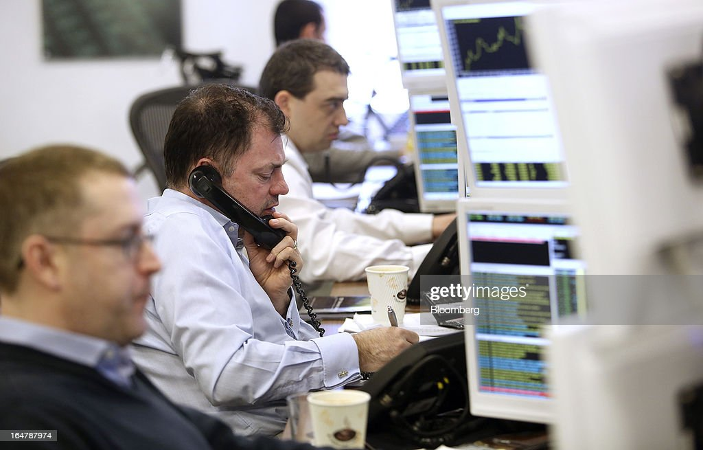 A stockbroker speaks on the telephone as he monitors financial data on his computer screens at Shore Capital Group Ltd. brokerage in London, U.K., on Thursday, March 28, 2013. Cyprus's banks opened for the first time in almost two weeks, with new rules curbing access to cash preventing an initial panic to withdraw deposits. Photographer: Chris Ratcliffe/Bloomberg via Getty Images