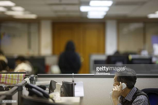 A stockbroker talks on a telephone at a securities brokerage in Hong Kong China on Friday Jan 15 2016 Asian stocks sank to a threeyear low as oil...