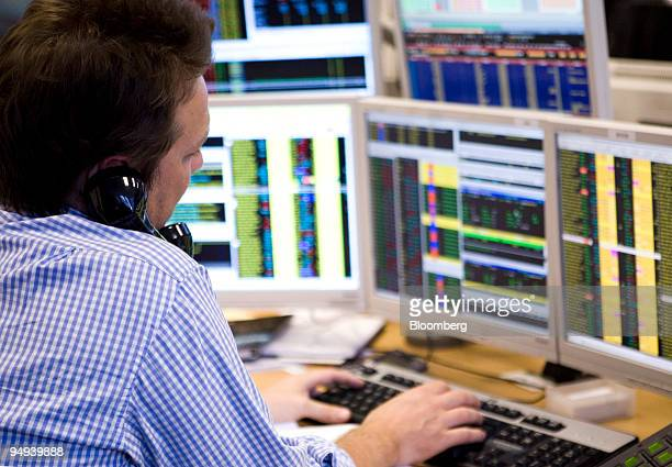 A stockbroker talks on the telephone while working on his computer at Shore Capital Markets in London UK on Tuesday March 3 2009 UK stocks retreated...
