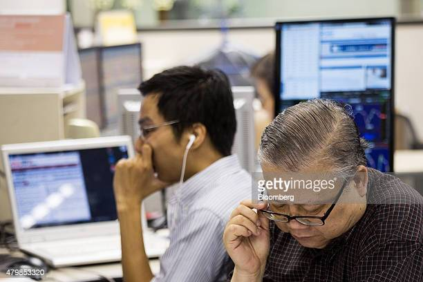 Stockbrokers and investors sit in front of screens displaying share prices at a securities brokerage in Hong Kong China on Wednesday July 8 2015...