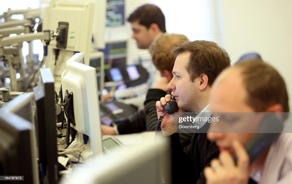 Stockbrokers speak on telephones as they monitor financial data on computer screens at Shore Capital Group Ltd. brokerage in London, U.K., on Thursday, March 28, 2013. Cyprus's banks opened for the first time in almost two weeks, with new rules curbing access to cash preventing an initial panic to withdraw deposits. Photographer: Chris Ratcliffe/Bloomberg via Getty Images