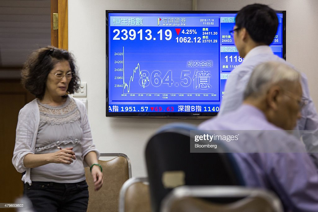 Stockbrokers walk past a screen displaying the Hang Seng Index figure at a securities brokerage in Hong Kong China on Wednesday July 8 2015 Investors...