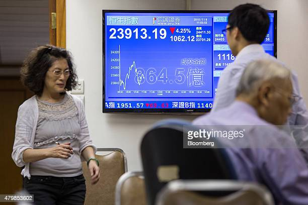 Stockbrokers walk past a screen displaying the Hang Seng Index figure at a securities brokerage in Hong Kong China on Wednesday July 8 2015 Investors...