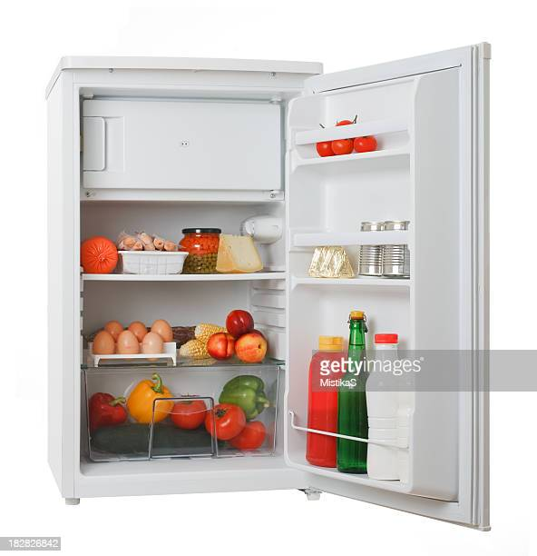 Stocked white mini fridge with produce and eggs