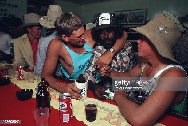 Stockhands including an aborigine joke around and drink at the bar of a pub in Camoweal in the evening after work They work on one of the outback...