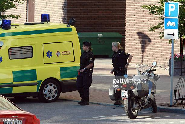 Police and ambulance are seen 02 July 2006 at the site where a man opened fire with an automatic weapon and wounded a woman in the leg in the north...