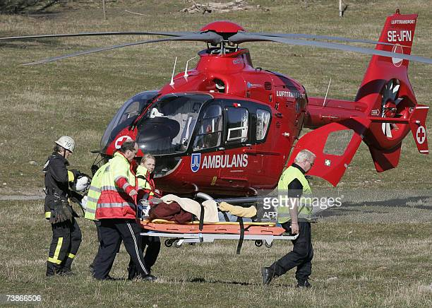 Rescue personnel carry one of the injured to a waiting ambulance helicopter after a Piper PA 28 private airplane crashed into a tree in the Fisksjo...
