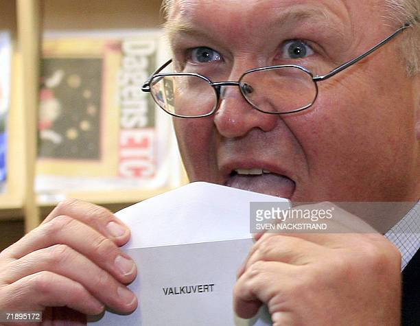 Swedish Prime Minister and Social Democrat leader Goeran Persson licks an envelope as he makes advance voting in a library in Stockholm 15 September...