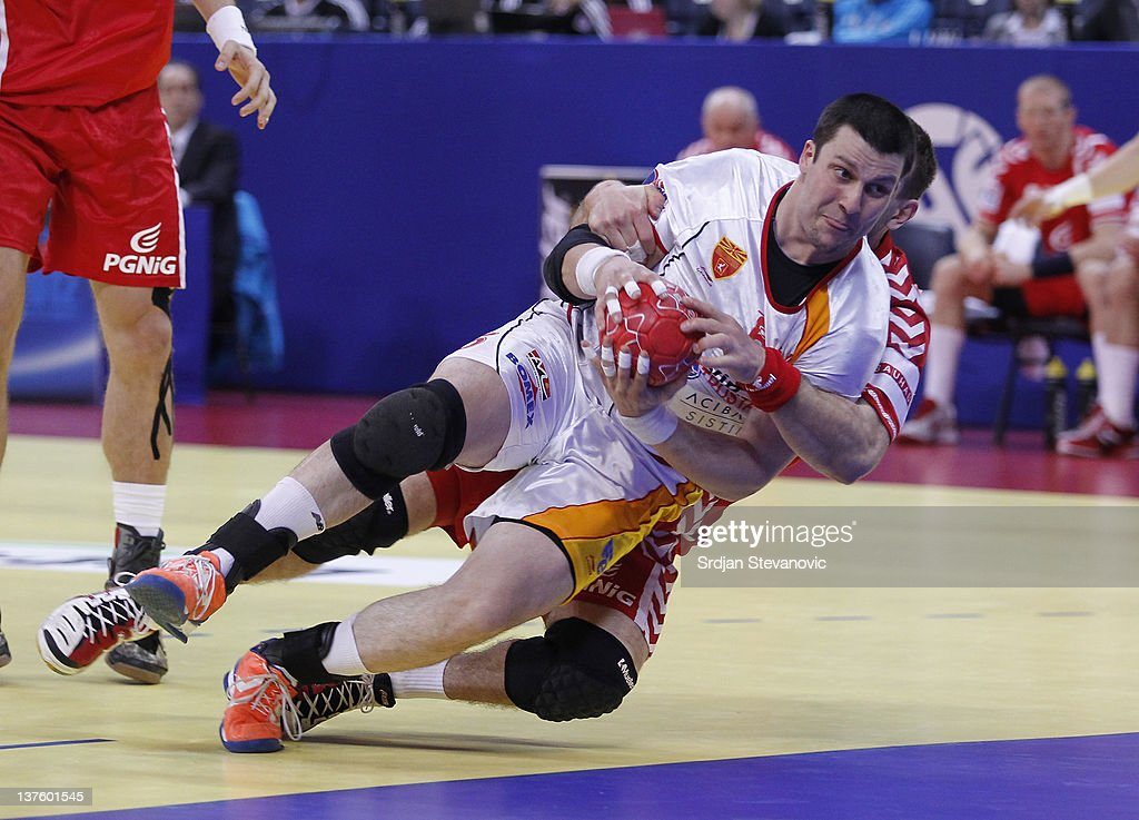 Stojanche Stoilov (C) of Macedonia is fouled by Bartosz Jurecki of Poland during the Men's European Handball Championship 2012 second round group one match between Poland and Macedonia, at Arena Hall on January 23, 2012 in Belgrade, Serbia.