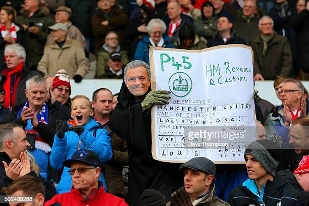 Stoke City fan wears a Jose Mourinho mask as he poses with a P45 for Louis van Gaal manager of Manchester United during the Barclays Premier League...
