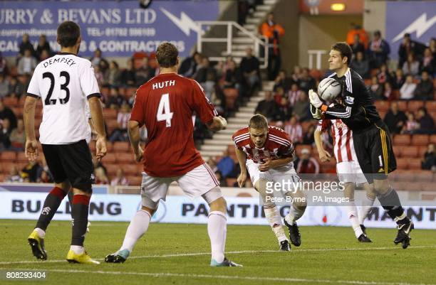 Stoke City goalkeeper Asmir Begovic fumbles with the ball before a shot on goal is taken by Fulham's Clint Dempsey