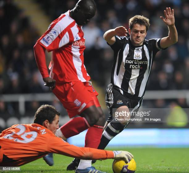 Stoke City goalkeeper Thomas Sorensen saves the ball from the feet of Newcastle United's Michael Owen