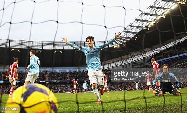 Stoke City keeper Asmir Begovic looks on as David Silva celebrates after team mate Yaya Toure has scored the winning goal during the Barclays Premier...