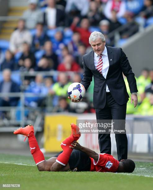 Stoke City manager Mark Hughes looks down at Cardiff City's Kevin Theophile Catherine after he was tackled by Stoke City's Glenn Whelan during the...