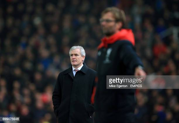 Stoke City manager Mark Hughes looks on from the touchline beyond Liverpool manager Jurgen Klopp