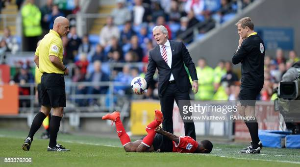Stoke City manager Mark Hughes looks towards referee Howard Webb as Cardiff City's Kevin Theophile Catherine lies on the floor after he was tackled...