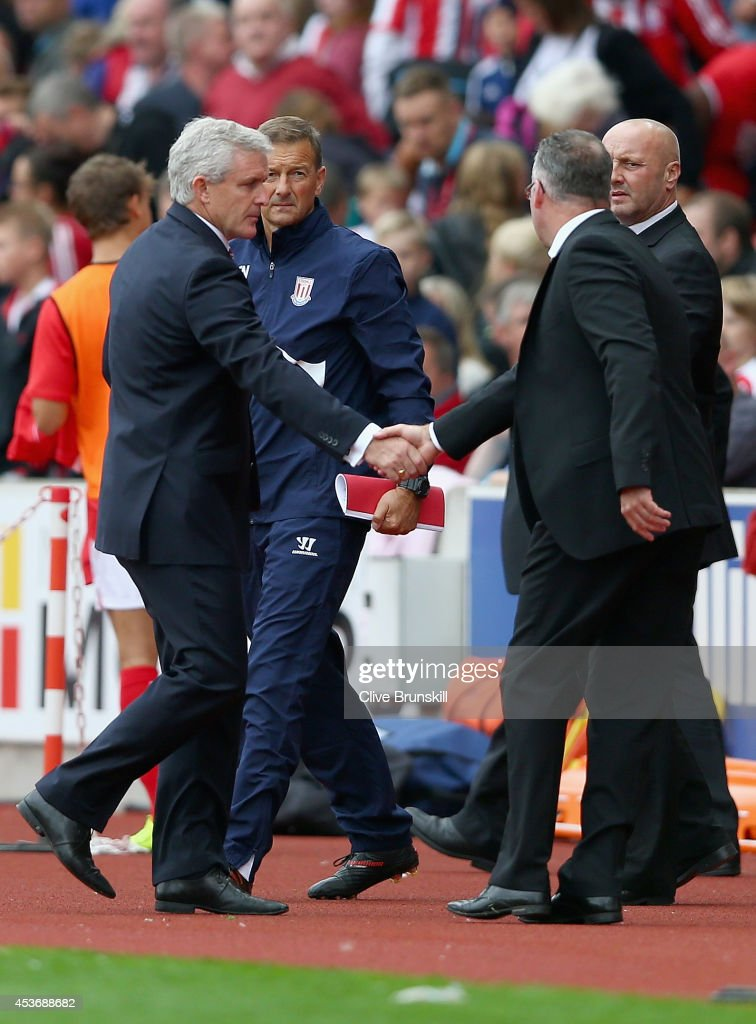 Stoke City manager Mark Hughes shakes hands with Aston Villa manager Paul Lambert at the final whistle of the Barclays Premier League match between Stoke City and Aston Villa at Britannia Stadium on August 16, 2014 in Stoke on Trent, England.