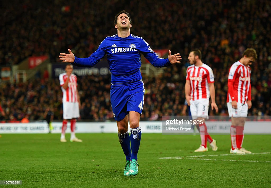 Stoke City players look dejected as Cesc Fabregas of Chelsea celebrates as he scores their second goal during the Barclays Premier League match...
