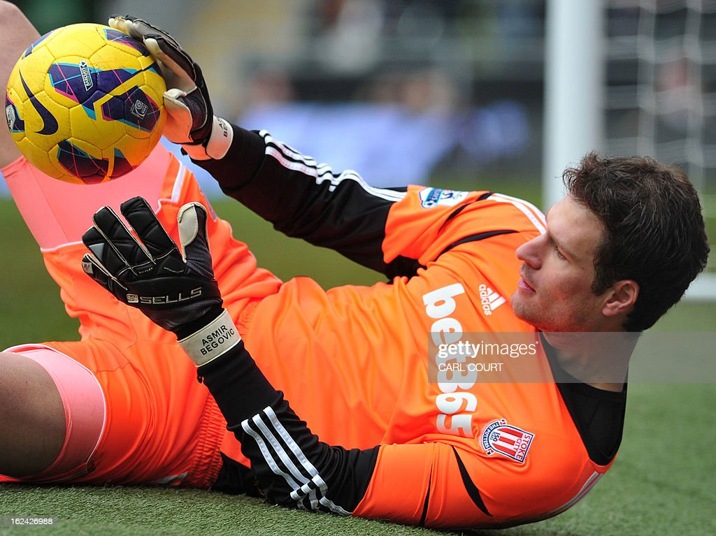"""Stoke City's Bosnian goalkeeper Asmir Begovic gathers the ball during the English Premier League football match between Fulham and Stoke City at Craven Cottage in London on February 23, 2013. Fulham won the game 1-0. USE. No use with unauthorized audio, video, data, fixture lists, club/league logos or """"live"""" services. Online in-match use limited to 45 images, no video emulation. No use in betting, games or single club/league/player publications"""