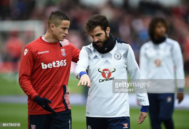 Stoke City's Dutch midfielder Ibrahim Afellay speaks with Chelsea's Spanish midfielder Cesc Fabregas before the English Premier League football match...
