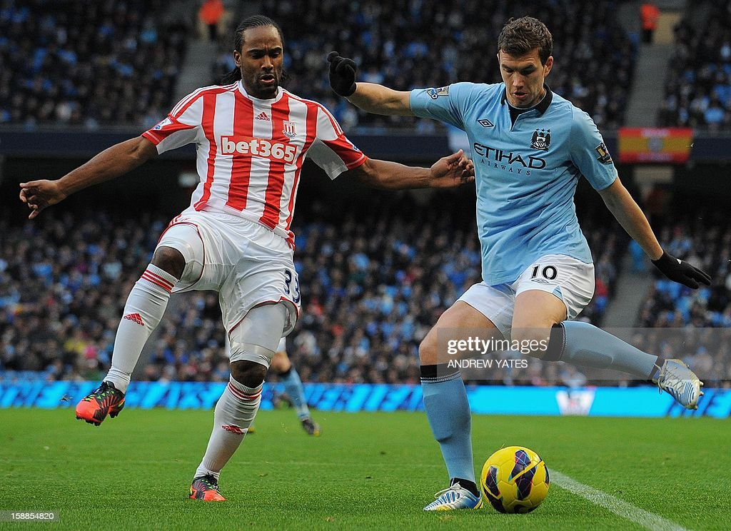 "Stoke City's English forward Cameron Jerome (L) vies with Manchester City's Bosnian forward Edin Džeko during the English Premier League football match between Manchester City and Stoke City at The Etihad stadium in Manchester, north-west England on January 1, 2013. USE. No use with unauthorized audio, video, data, fixture lists, club/league logos or ""live"" services. Online in-match use limited to 45 images, no video emulation. No use in betting, games or single club/league/player publications."