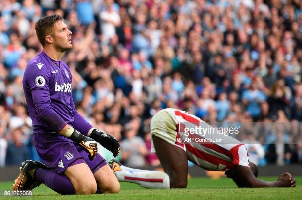 Stoke City's English goalkeeper Jack Butland and Stoke City's French defender Kurt Zouma react after Manchester City score their seventh goal during...