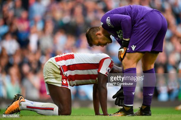 Stoke City's English goalkeeper Jack Butland helps up Stoke City's French defender Kurt Zouma after Machester City's seventh goal during the English...