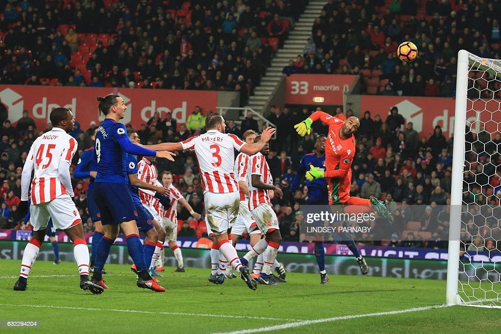 Stoke City's English goalkeeper Lee Grant (R) looks back as he dives to see the ball go into his goal from a free kick hit by Manchester United's English striker Wayne Rooney (L obscured) for Rooney to score an equalising goal for 1-1 and his 250th goal for Manchester United making him the club's all-time record scorer during the English Premier League football match between Stoke City and Manchester United at the Bet365 Stadium in Stoke-on-Trent, central England on January 21, 2017. / AFP / Lindsey PARNABY / RESTRICTED TO EDITORIAL USE. No use with unauthorized audio, video, data, fixture lists, club/league logos or 'live' services. Online in-match use limited to 75 images, no video emulation. No use in betting, games or single club/league/player publications. /
