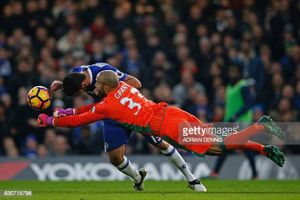 TOPSHOT Stoke City's English goalkeeper Lee Grant makes a save as Chelsea's Brazilianborn Spanish striker Diego Costa prepares to open the scoring...