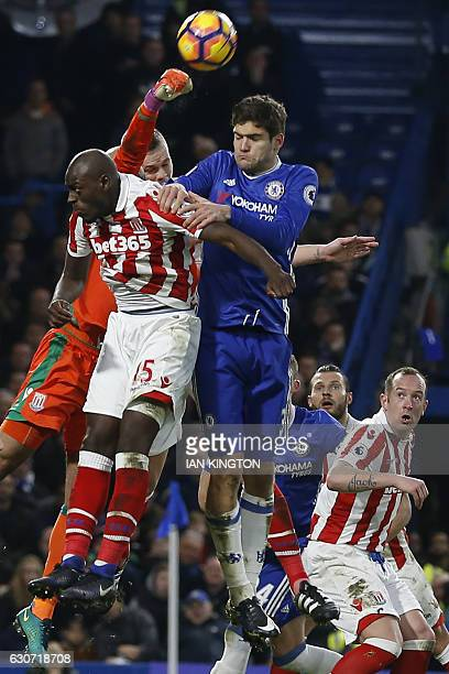 Stoke City's English goalkeeper Lee Grant punches the ball clear under pressure from Chelsea's Spanish defender Marcos Alonso during the English...