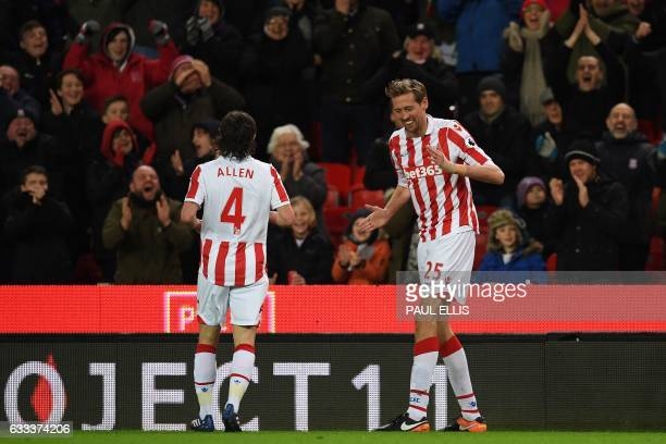 Stoke City's English striker Peter Crouch celebrates scoring his team's first goal and his 100th premiere league goal during the English Premier...