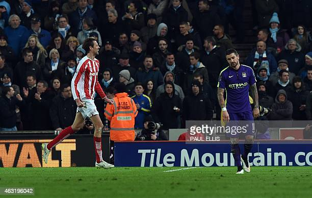 Stoke City's English striker Peter Crouch celebrates scoring their first goal as Manchester City's Serbian defender Aleksandar Kolarov reacts during...