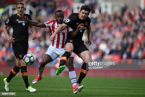 Stoke City's English striker Saido Berahino vies for the ball with Hull City's English defender Harry Maguire during the English Premier League...
