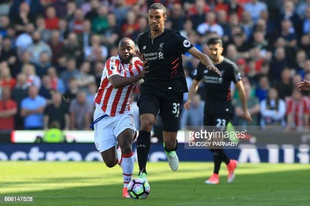 Stoke City's English striker Saido Berahino vies with Liverpool's Germanborn Cameroonian defender Joel Matip during the English Premier League...