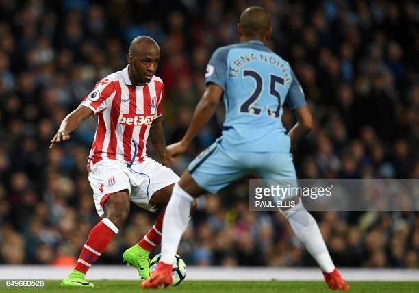 Stoke City's English striker Saido Berahino vies with Manchester City's Brazilian midfielder Fernandinho during the English Premier League football...