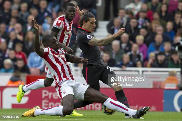 Stoke City's French defender Kurt Zouma slides in to make a tackle on Arsenal's Spanish defender Hector Bellerin during the English Premier League...