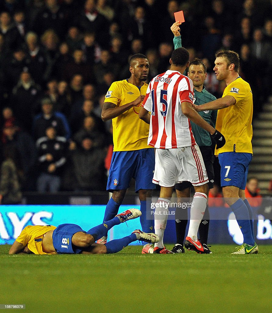 """Stoke City's French midfielder Steven N'Zonzi (3rd R) is shown a red card by referee Mark Clattenburg (2nd R) after a foul on Southampton's English midfielder Jack Cork (L) during the English Premier League football match between Stoke City and Southampton at The Britannia stadium, Stoke-on-Trent, England, on December 29, 2012. The game ended 3-3. USE. No use with unauthorized audio, video, data, fixture lists, club/league logos or """"live"""" services. Online in-match use limited to 45 images, no video emulation. No use in betting, games or single club/league/player publications."""