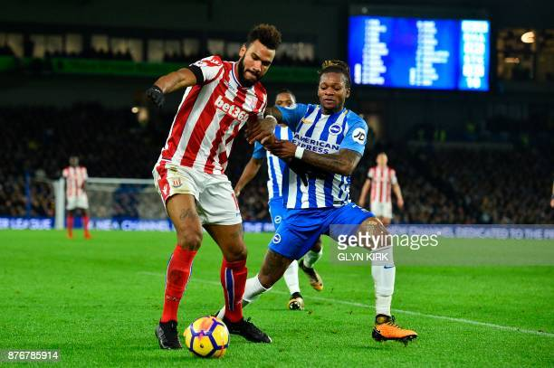 Stoke City's German midfielder Eric Maxim ChoupoMoting holds off Brighton's Cameroonian defender Gaetan Bong to get his cross in during the English...