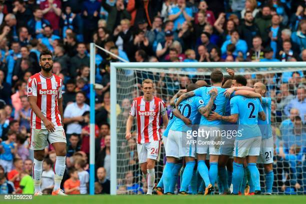 Stoke City's German midfielder Eric Maxim ChoupoMoting reacts as Manchester City players celebrate their sixth goal during the English Premier League...