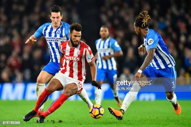 Stoke City's German midfielder Eric Maxim ChoupoMoting takes on Brighton's English defender Lewis Dunk and Brighton's Cameroonian defender Gaetan...
